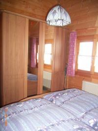 Dieses Schlafzimmer ist mit einem Doppelbett und großem Kleiderschrank bestückt. - Bild 7: AWM-Ferienhaus im Bayerischen Wald, gemütliches Holzblockhaus mit Kaminofen