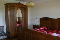 Im Schlafzimmer im Erdgeschoss befindet sich ein antikes Doppelbett, zwei Nachttischchen, ein großer Kleiderschrank, sowie eine Wäschekommode. - Bild 7: Ferienhaus Beestland am Rande der Mecklenburgischen Schweiz für 6 Personen