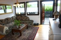 Auch durch die große Fensterfront des Wohnzimmers genießen Sie die Fernsicht. Eine komfortable Sitzecke (m. Schlaffunktion) lädt zum gemütlichen Erzählen, Planung von Ausflügen oder einfach zum Entspannen ein. - Bild 7: Idyll. Ferienhaus EifelNest Fernsicht & uneinsehbare Sonnenterrasse & WLAN